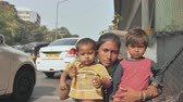 étnico : Mumbai, India - December 17, 2018: A homeless young Indian mom with her children on the streets of Mumbai.