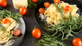 saláta : Delicious pasta in black plates on wooden board next to cherry tomatoes, cheese and greenery