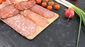 salami slice : Delicious sliced italian antipasto appetizers on wooden board. Top view Stock Footage