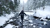 opatrný : Man walking on rocks in winter river. Travel and adventure Dostupné videozáznamy