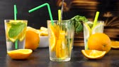 citrus fruit recipe : Pouring water in a glass with fresh cutted slices of oranges. Vitamin water. Slow motion footage