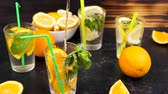 citrus fruit recipes : Pouring water in a glass with slices of oranges next to glasses with lemonade. Slow motion footage