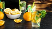 citrus fruit recipes : Fresh orangeade water next to glasses with lemonade, lemons and oranges on a wooden board