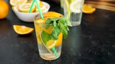citrus fruit recipe : Delicious orangeade with mint in a glass on a wooden board next to cutted oranges it was made of Stock Footage