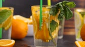 citrus fruit recipes : Blowing bubbles in a glass with vitamin water and slices of orages. 180fps slow motion footage