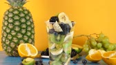 ananas : Fresh healthy and delicious dessert made of sliced fruits in platic cup on yellow background. Zoom in from out of focus to in focus dolly footage Dostupné videozáznamy
