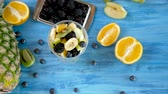 смешивать : Fresh healthy summer diet of fruit salad in plastic cup on vintage blue background. Top view dolly footage