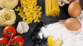 setas : Spaghetti, pasta and uncooked macaroni on dark table next to ingredients for dinner