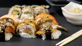 ノリ : Dolly slide shot of delicious and healthy sushi rolls on black stone background