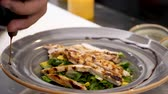 abacate : Pouring souce on avocado salad with grilled chicken meat in restaurant kitchen