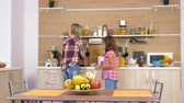 juntar : Mother and daughter in the kitchen arranging the table for meal Stock Footage