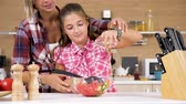 does : Young girl pouring oil in salad in a glass bowl in the kitchen. Slow motion 4K footage