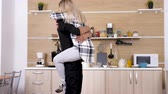 ırklararası : Beautiful blonde woman jumps in arms of her husband in the kitchen. Interracial couple love. Shot on dolly slider in 4K UHD