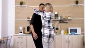 ırklararası : Woman jumps in her boyfriends arms at the kitchen. Beautiful interracial couple having fun at home Stok Video