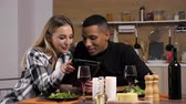 ırklararası : Beautiful happy couple having candle light dinner and looking at digital tablet PC screen while at the table in their kitchen. Interracial couple. Dolly slider 4K footage with parallax effect Stok Video