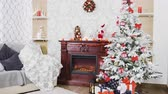lareira : Decorated Christmas Interior. There is a beautiful white christmas tree with gift boxes under it and a fireplace with toys and decorations on it. Stock Footage