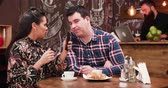meghitt : Couple on a date in stylish coffee shop pub restaurant drinking coffee and looking something on smartphone. A bearded waiter in the background is working at the counter