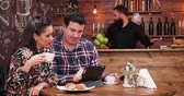 intimo : Couple using a digital tablet PC in vintage coffee shop with wooden walls and rustic interior. There is a bearded bartender working in the background at the counter