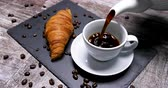 kruvasan : Serving a cup of coffee with a croissant on a black board. Pouring some coffee from a pot. Stok Video