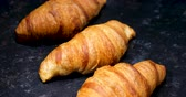 vařené : Revealing shot of croissants in row. Freshly backed croissants on a black background.