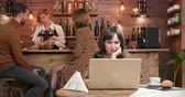 blogger : Young woman in a restaurant reading a text on her laptop. camera advancing on a very concetrated young female