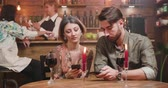 distraído : A young careless couple distracted by their smartphones while on a date. The bad effects of social media