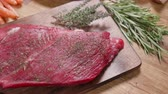 sangrento : Slowly revealing a fresh raw chunk of meat on an aged wooden board. Wooden background decorated with thyme and rosemary.