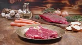 sangrento : Slow slide movement showing two pieces of raw meat and vegetables on a wooden background. Vintage looking bronze plate and wooden board.