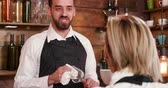 serveuse : Handheld medium shot of a young bearded bartender. Bartender talking and telling a story to a blonde waitress.
