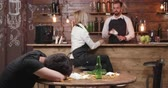 serveuse : Witress tries to wake a drunk costomer that got sick. A costumer got drunk and keeps his head on the messy table. Vidéos Libres De Droits