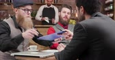 desenvolver : Attractive bearded man signing trading contract with new partners. Young hipster freeancers over a meeting in a coffee shop. Vídeos