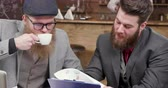 desenvolver : Two stylish males enjoy coffee during a business meeting