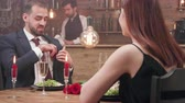 engagé : Young woman receiving a marriage proposal at a dinner date. Love and marriage. Couple in love decides to become a family. Vidéos Libres De Droits