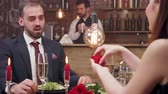engagé : Young woman asking her boyfriend to get married at a romantic dinner. Couple at a date in the restaurant. Woman offers man to get engaged.