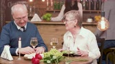 отношения : Cheerful senior couple on a romantic date in a restaurant. Old man and woman enjoying a dinner on a romantic date.
