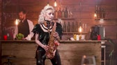caz : Beautiful woman in black stage costume playing a melody on saxophone. Bar background and a bartender enjoying the performance.
