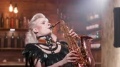 sax : Female saxophonist performs a song in a small jazz cafe. Singing at a private jazz party. Bartender enjoying the music.