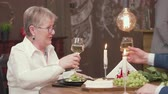 coqueteando : Mature lady clinking glasses with her partner. Old couple on a date in vintage restaurant. Grapes, cheese and wine on wooden table.