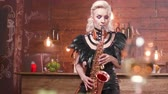 sax : Nice female saxophonist with bright make up performs in a restaurant. Jazz blues solo concert in a small restaurant. Stock Footage