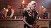 saksofon : Woman in sexy leather clothes on a high bar chair playing at a saxophone