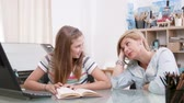 role : Teenage girl reads a text to her mother as she listens carefully. Mom listening to her daughters reading skills.