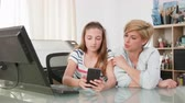 interni casa : Young teenage girl showing something to her mother on a smartphone. Mom and teenage daughter looking at a smartphone screen.