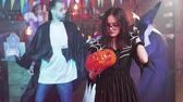 резной : Young attractive girl in witch costume dances with a jack-o-lantern in her hands. Friends at a halloween party in different costumes.