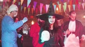 disfarçar : Young woman disguised in witch costume hold a skull in her hands at a halloween party