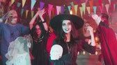 disfarçar : Young woman with a beautiful smile dances disguised as a witch at a halloween party Stock Footage