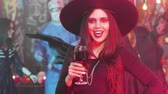 disfarçar : Woman dressed in evil witch costume drinks blood from a glass Stock Footage