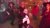 vampiro : Young man in evil vampire costume dancing in the middle of a group of friends celebrating halloween. Gang of friends in scary outfits having fun at a party. Vídeos
