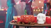 tomada : People in halloween costumes dancing in the background of holiday elements decorations. Jack-o-lantern, skull, spider and candles on a wooden table.