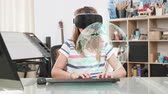 ar : Kid at home doing her homework in a virtual space by wearing a VR headset and typing on the keyboard while a virtual holographic globe is displayed in front of her. Stock Footage