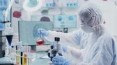 pharmaceutical factory : In high end modern research facility two chemists are working with colored liquid samples Stock Footage